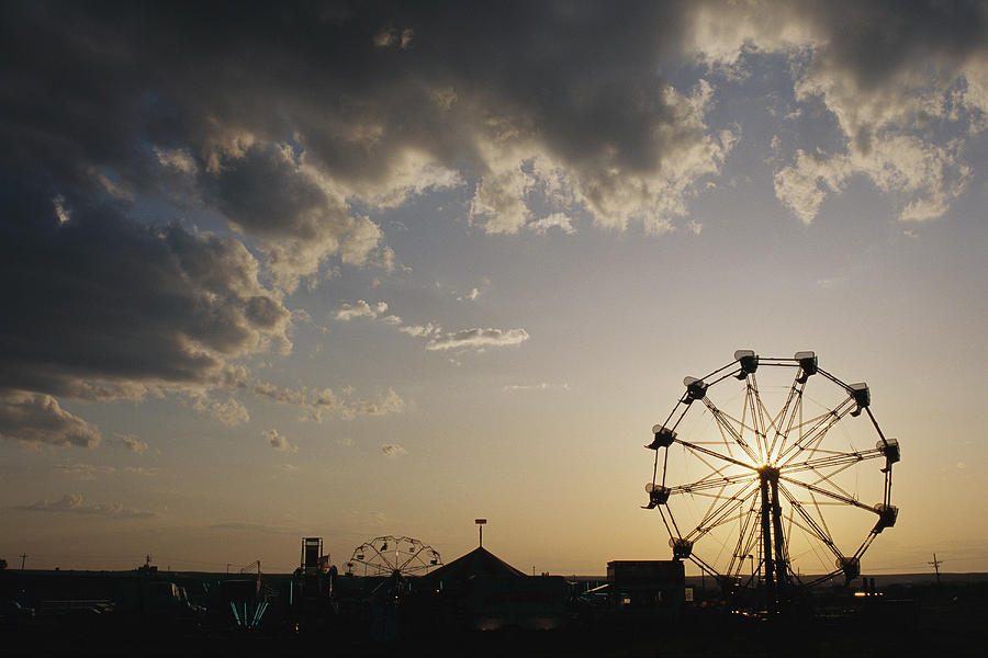 A Ferris Wheel Is Silhouetted Photograph