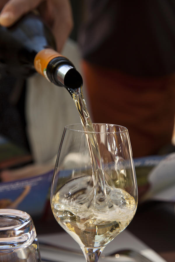A Glass Of White Wine Being Poured Photograph