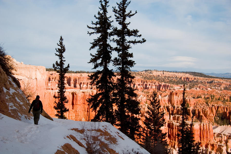 A Hiker Walks Along A Ledge In Winter Photograph