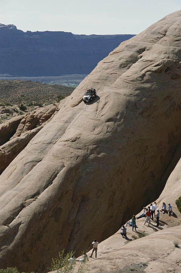 Lion's Back Rock Photograph - A Jeep Drives Down A Slick Rock by James P. Blair