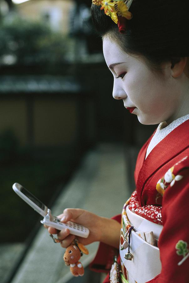 A Kimono-clad Geisha Dials Her Cell Photograph