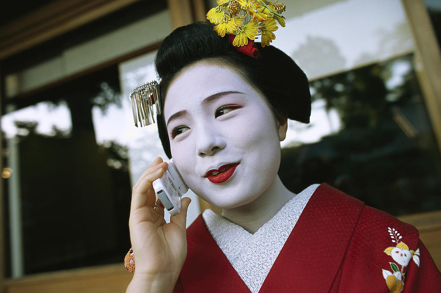 A Kimono-clad Geisha Talks On A Cell Photograph