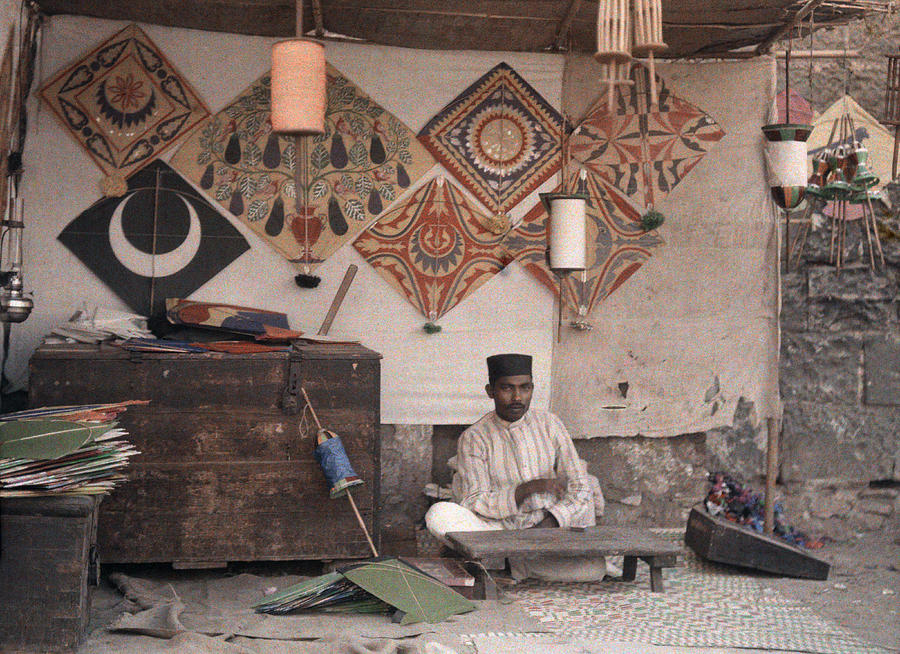 A Kite Merchant Sits In His Store Photograph