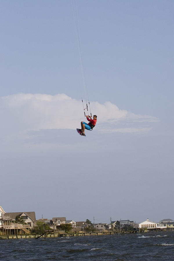 A Kiteboarder Jumps High Over Beach Photograph
