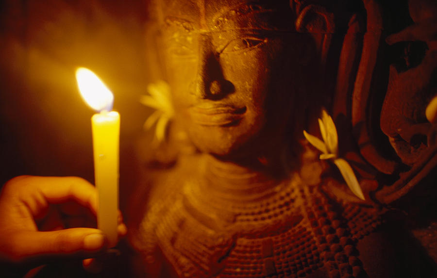 A Man Holds A Candle Up To A Stone Photograph