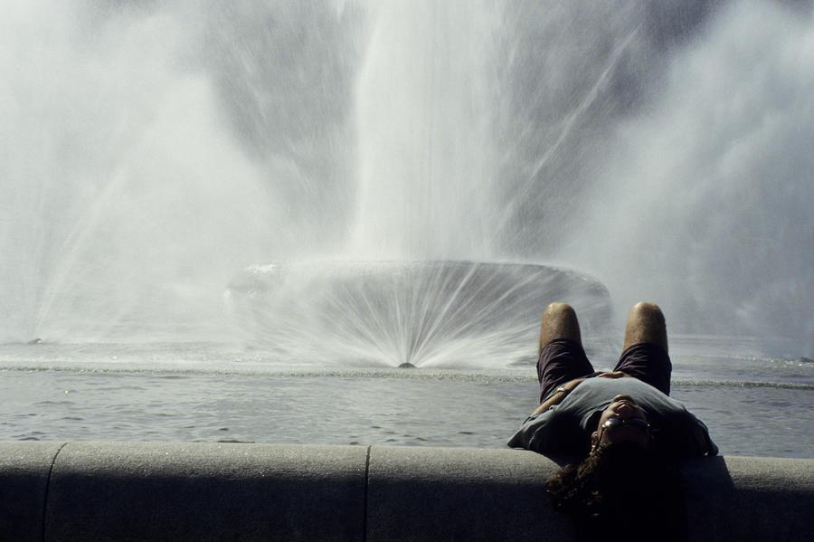 A Man Relaxes At A Fountain Photograph