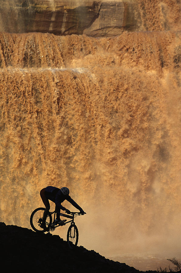 A Mountain Biker Pedals Past Rushing Photograph
