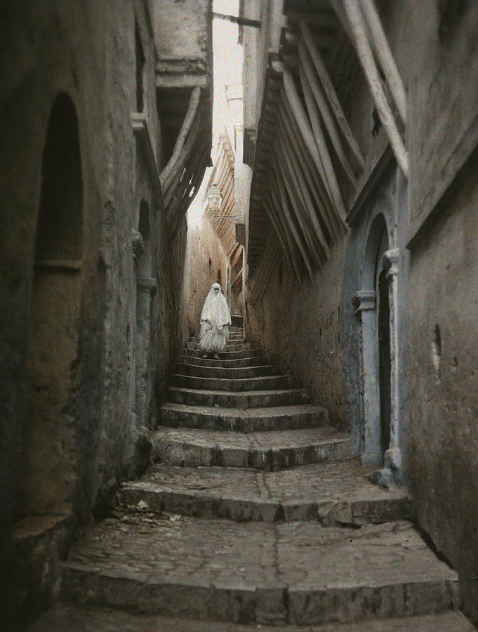 Day Photograph - A Muslim Woman Walking Down A Steep by Gervais Courtellemont