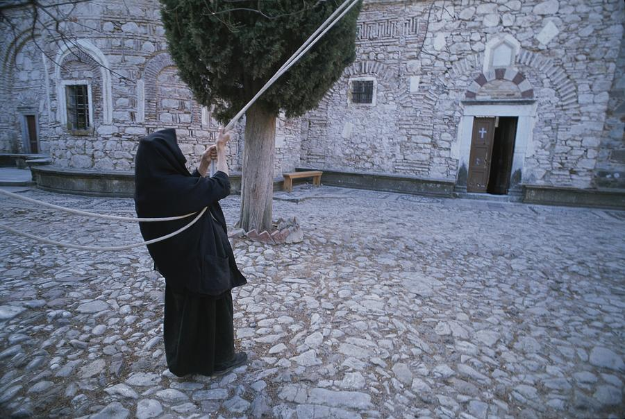 A Nun Pulls On Ropes In A Courtyard Photograph