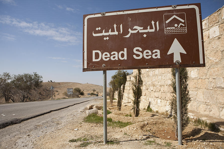 A Road Sign In Both Arabic And English Photograph