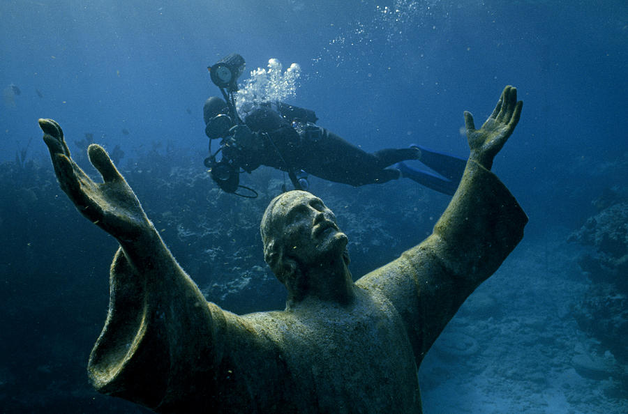 A Scuba Diver Swims Past The Statue Photograph