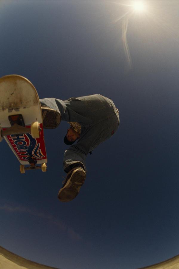 A Skateboarder Jumping At A Skate Park Photograph