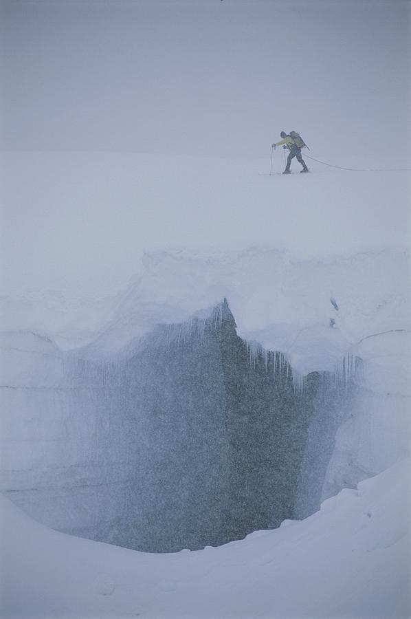 A Skier Above A Deep Glacier Crevasse Photograph