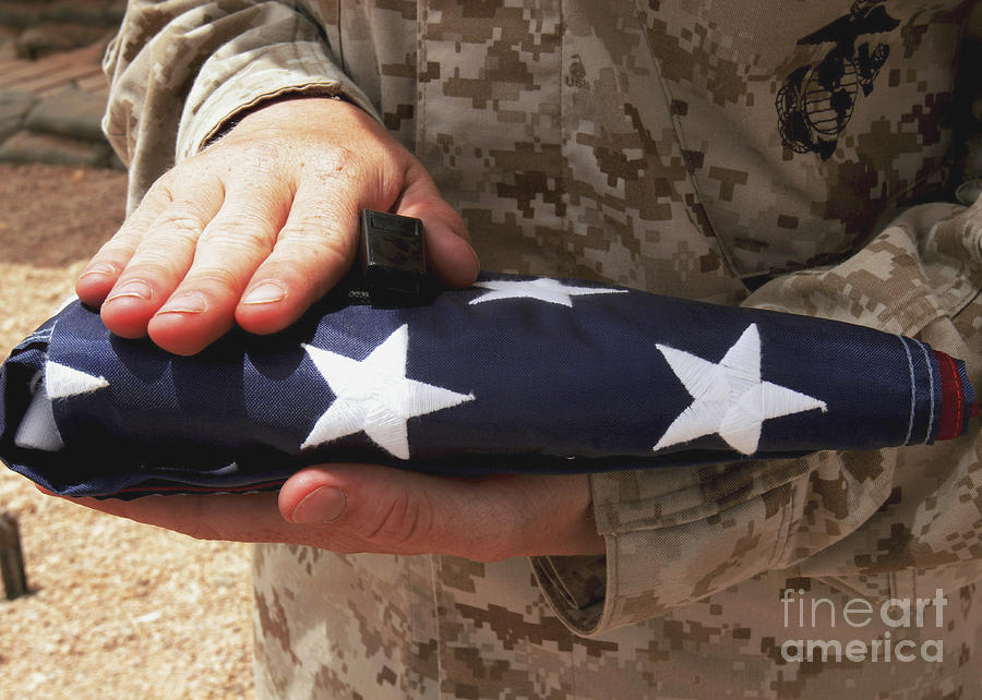 A Soldier Holds The United States Flag Photograph