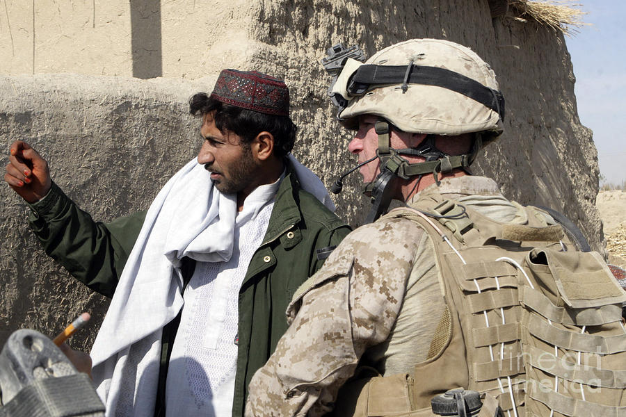 A Soldier Talks To A Local Villager Photograph
