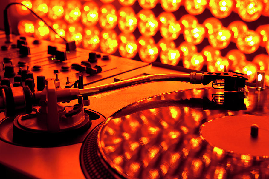 A Turntable And Sound Mixer Illuminated By Lighting Equipment Photograph  - A Turntable And Sound Mixer Illuminated By Lighting Equipment Fine Art Print