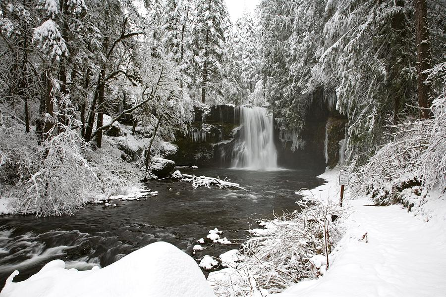 A Waterfall In To A River In Winter Photograph