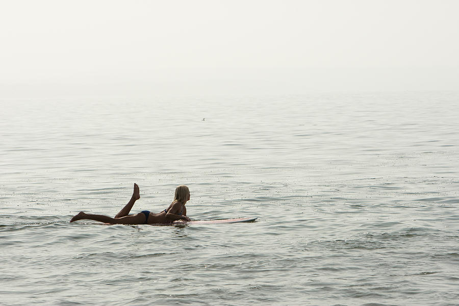 A Woman Rests On Her Surfboard Waiting Photograph