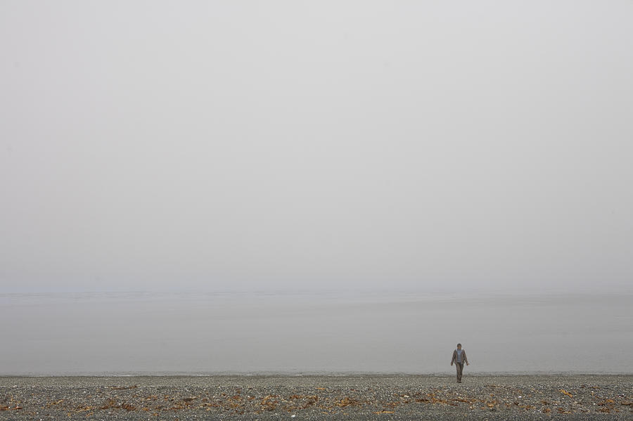 A Woman Walks Along The Beach Photograph