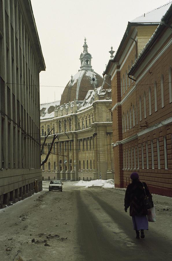 A Woman Walks Down A Snowy  Street Photograph