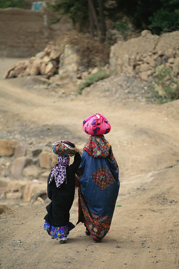 A Yemeni Woman And Child Carrying Photograph