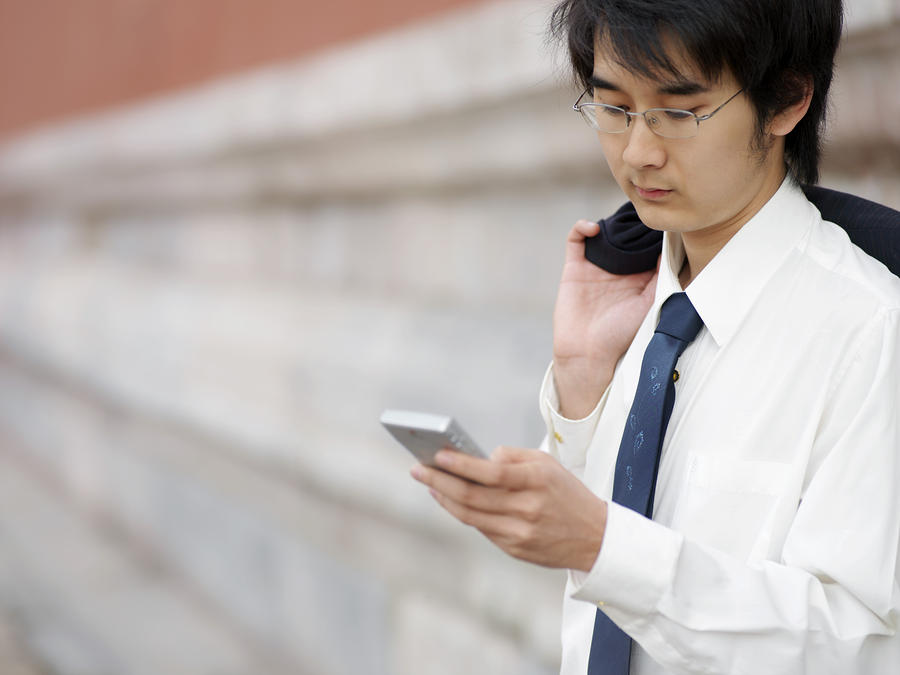 A Young Businessman Checks His Text Photograph