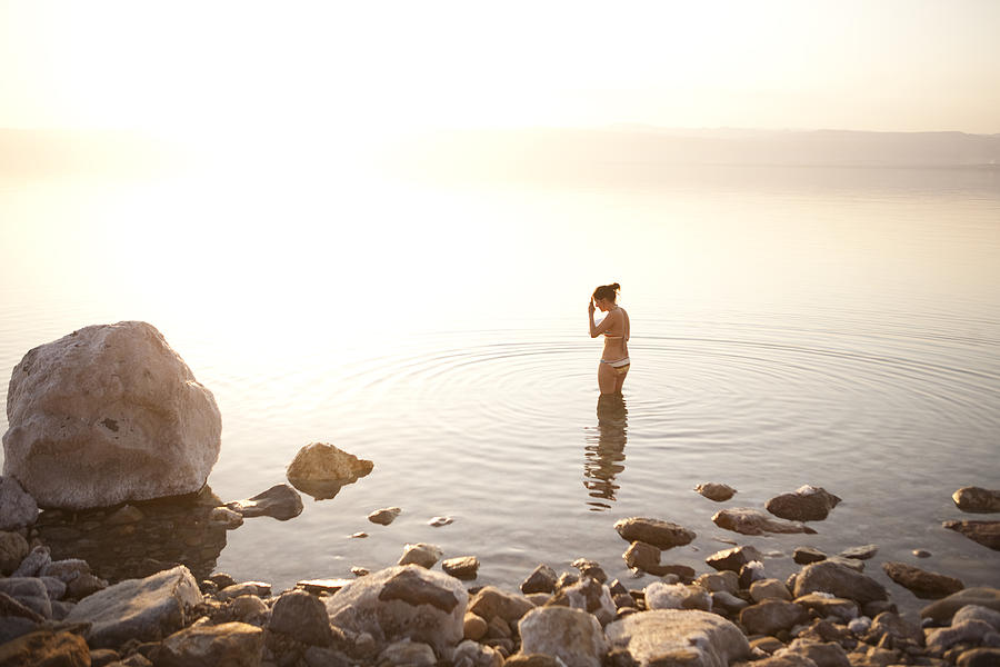 A Young Woman Wades Into The Dead Sea Photograph