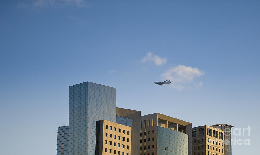 Air Travel Photograph - Airplane Flying Over Office Buildings by Noam Armonn
