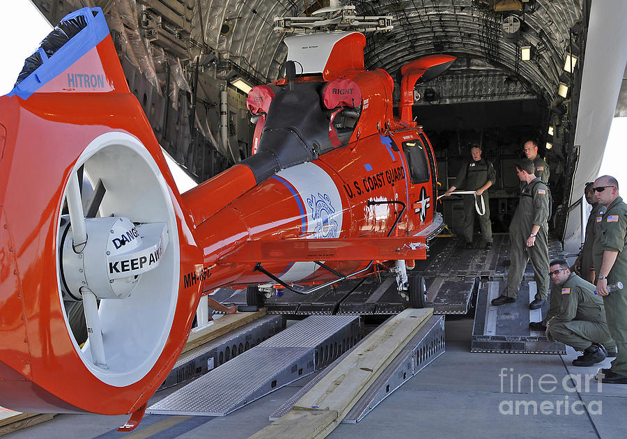 An Aircrew Loads A Coast Guard Hh-65 Photograph