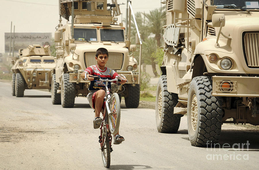 Military Photograph - An Iraqi Boy Rides His Bike Past A U.s by Stocktrek Images