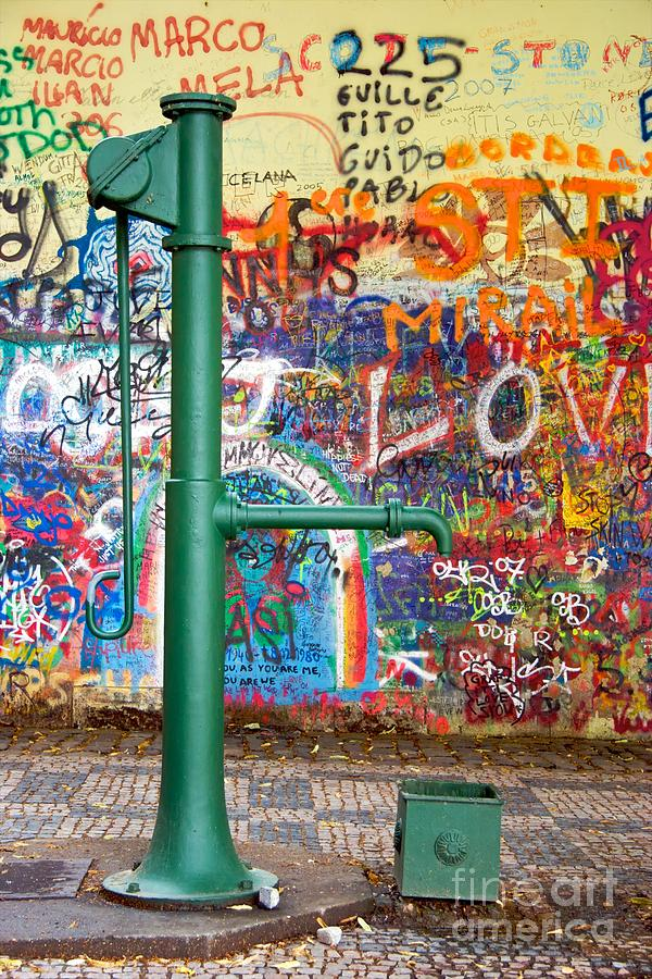An Old Pump And Lennon Wall In Prague Photograph