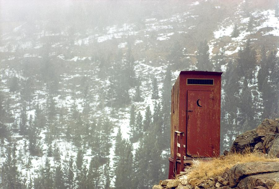 An Outhouse Perches On A Hillside Photograph