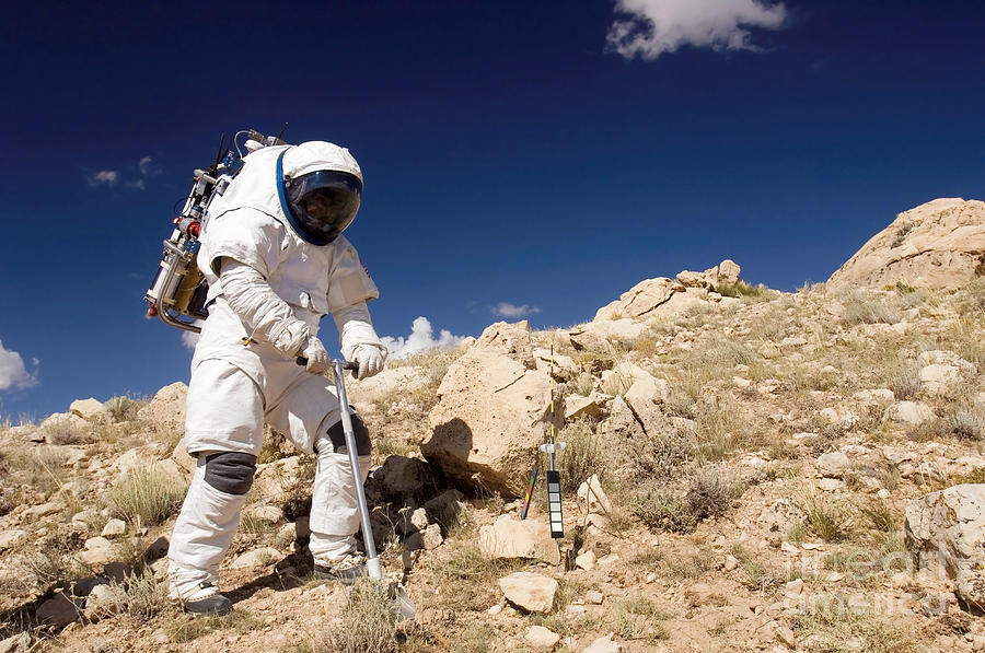 Astronaut Stands Beside A Core Sampling Photograph
