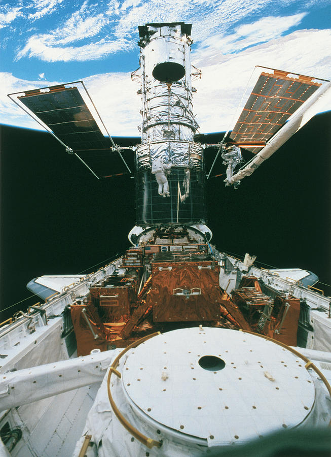 Vertical Photograph - Astronauts Of The Space Shuttle Working On A Satellite In Space by Stockbyte