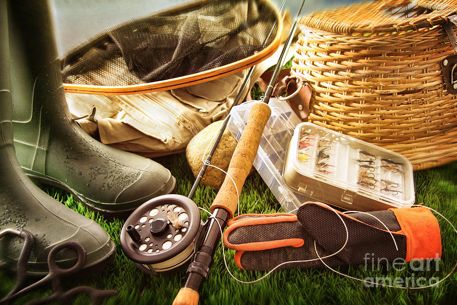 boots and fly fishing equipment on grass photograph by