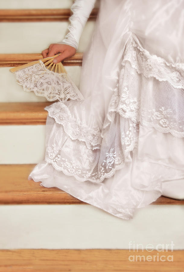 Bride Sitting On Stairs With Lace Fan Photograph