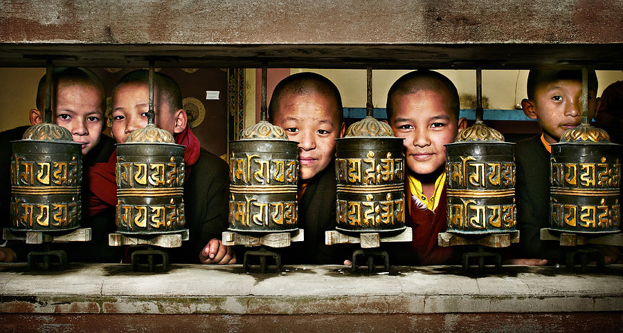 Buddhist Monks In Red Robes Look Out Of The Prayer Wheels With M Photograph  - Buddhist Monks In Red Robes Look Out Of The Prayer Wheels With M Fine Art Print