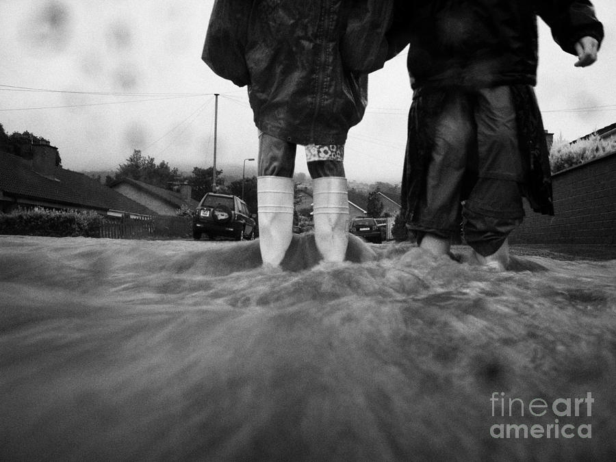 Children Walking In Heavy Rain Storm In The Street Photograph  - Children Walking In Heavy Rain Storm In The Street Fine Art Print