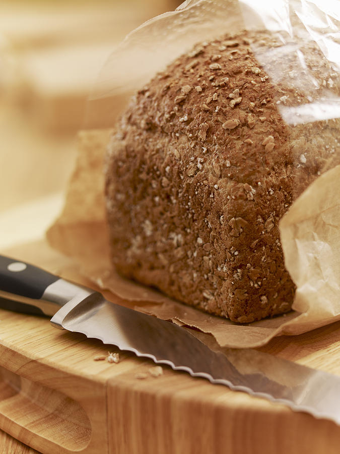 Close Up Of Knife And Loaf Of Bread In Wrapper Photograph