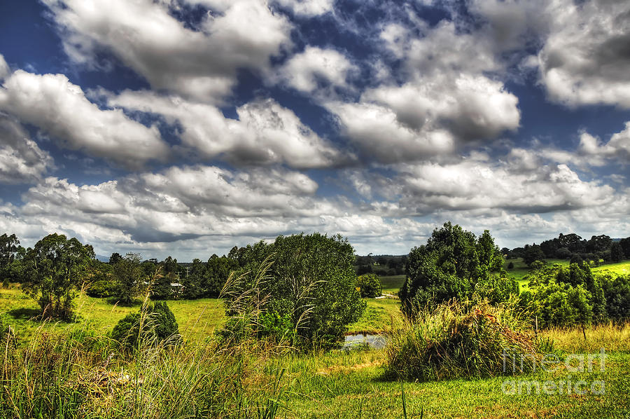 Clouds Floating Over Green Countryside Photograph