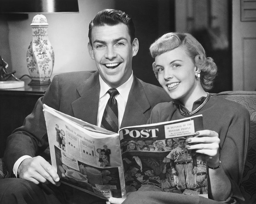 Couple Sitting On Sofa, Holding Magazine, (b&w), Portrait Photograph