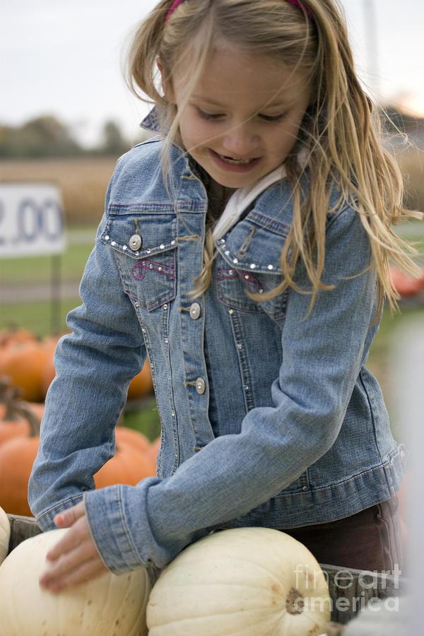 Vertical Photograph - Cute Little Girl Picking A Pumpkin by Christopher Purcell