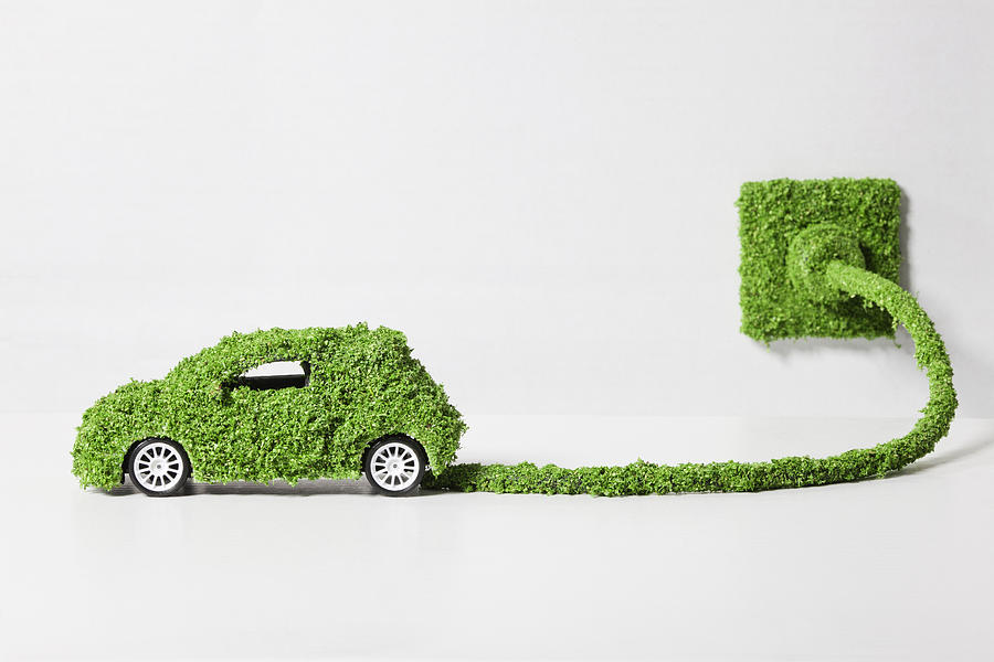 Electric Car Covered With Grass Connected To Socket, Close Up Photograph
