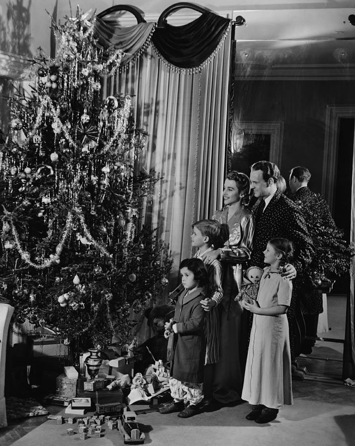 Family With Three Children (4-9) Standing At Christmas Tree, (b&w) Photograph
