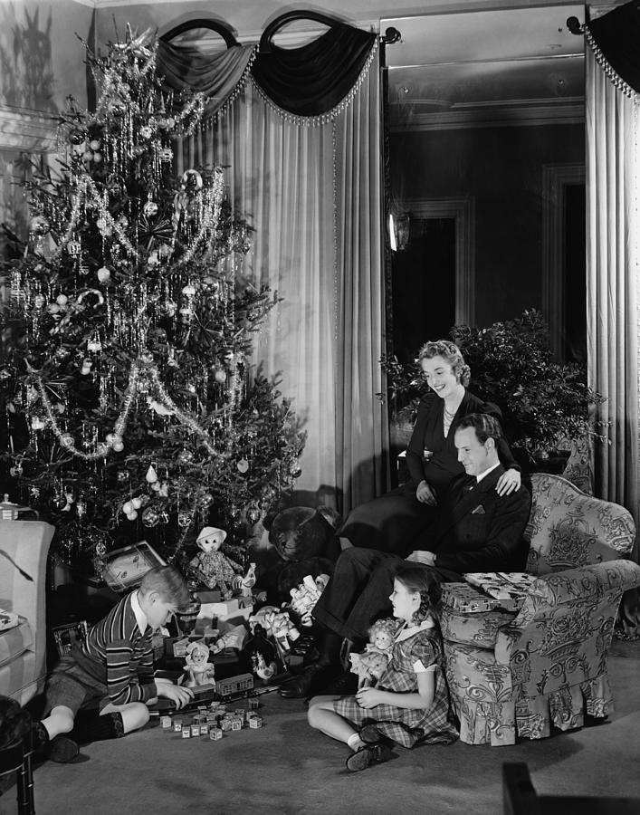 Family With Two Children (6-9) Sitting At Christmas Tree, (b&w) Photograph  - Family With Two Children (6-9) Sitting At Christmas Tree, (b&w) Fine Art Print