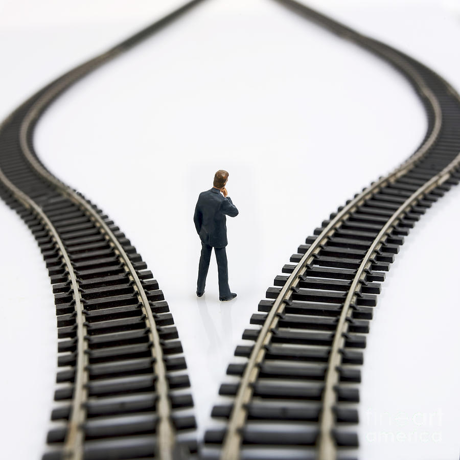 Figurine Between Two Tracks Leading Into Different Directions  Symbolic Image For Making Decisions Photograph  - Figurine Between Two Tracks Leading Into Different Directions  Symbolic Image For Making Decisions Fine Art Print
