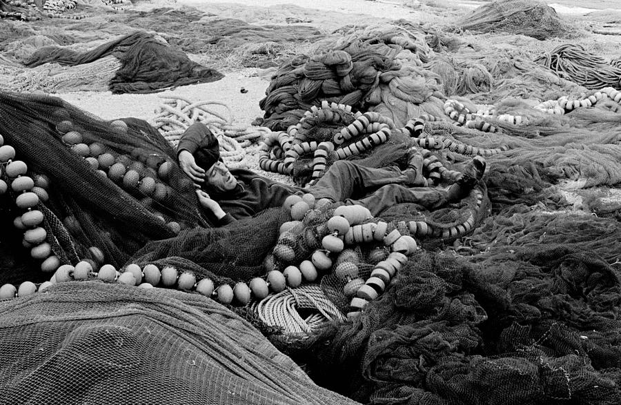 Fisherman Sleeping On A Huge Array Of Nets Photograph