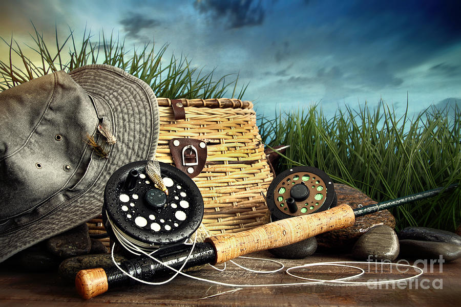 fly fishing equipment with hat on wooden dock photograph