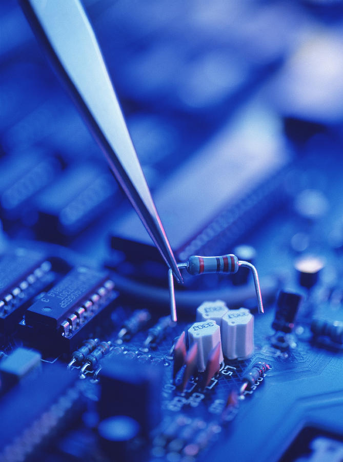 Forceps Holding A Resistor Over A Circuit Board Photograph