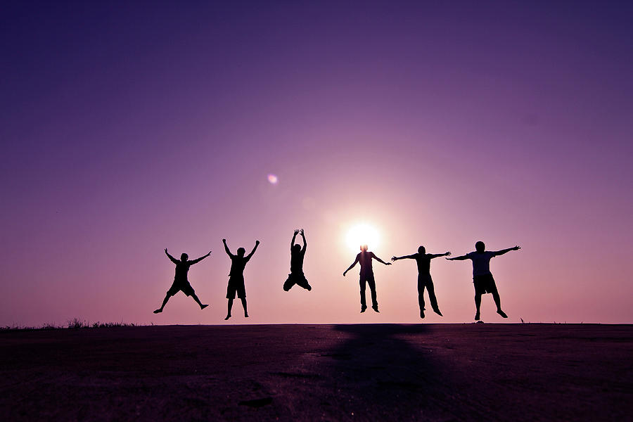 Friends Jumping Against Sunset Photograph